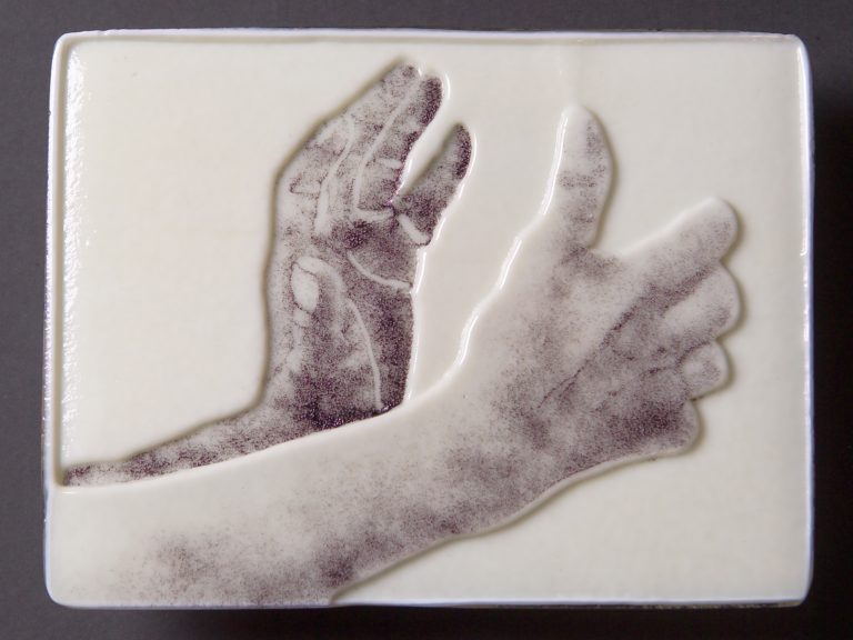 Carved glass panel of hands